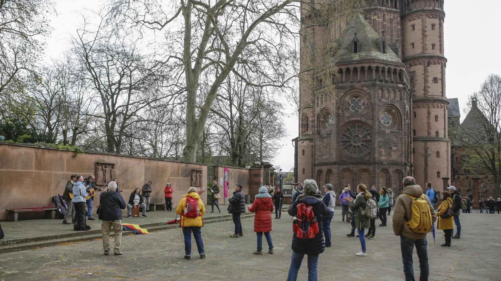 Menschen haben sich im Schatten der Kathedrale von Worms zu einem illegalen Gottesdienst versammelt.