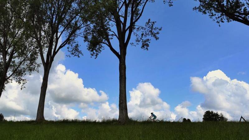 Eine Frau fährt auf ihrem Fahrrad vor dem teilweise mit Wolken überzogenen Himmel. Foto: Karl-Josef Hildenbrand/dpa/Symbolbild