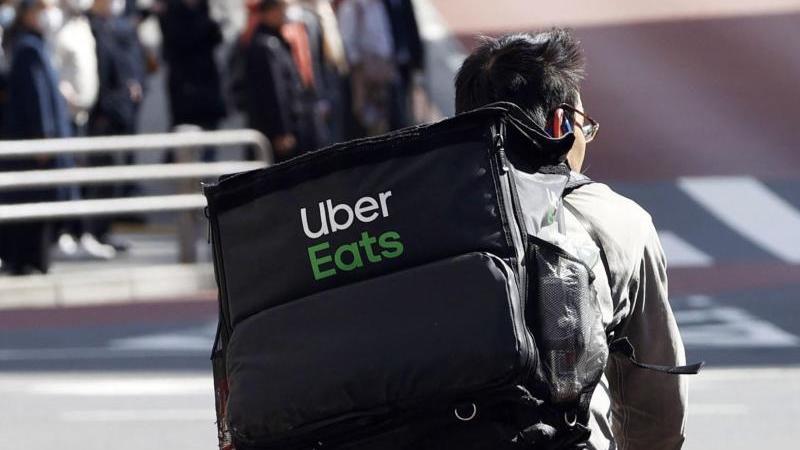 Ein Mitarbeiter des Essenslieferdienstes Uber Eats radelt mit einer Lieferung durch die Stadt.