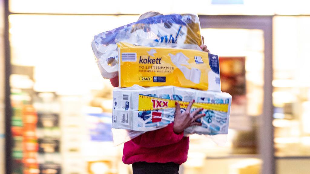 05.11.2020, Hamburg: Ein Frau läuft mit dem Arm voller Klopapierrollen aus einem Drogeriemarkt heraus. Gähnend leere Regale, wo sonst das Toilettenpapier thronte, waren im März dieses Jahres keine Seltenheit in deutschen Supermärkten. Weil viele der