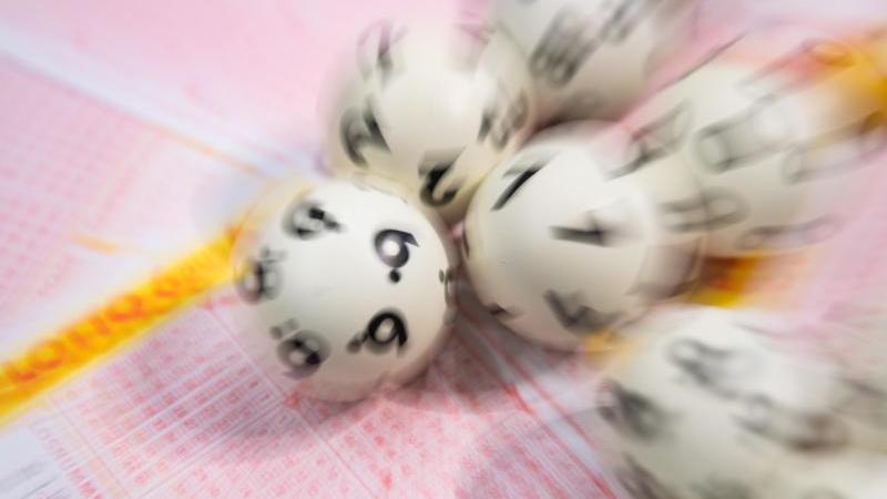 Lotto-Kugeln liegen auf einem Lottoschein (gestellte Szene - Aufnahme mit Zoomeffekt). Foto: Tom Weller/dpa/Archivbild