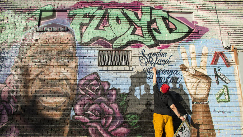 Daryel Simmons reaches up to touch the names of Sandra Bland and Breonna Taylor as she came to a George Floyd memorial mural after learning of the guilty verdict on all counts in the murder trial of former Minneapolis Officer Derek Chauvin in the dea