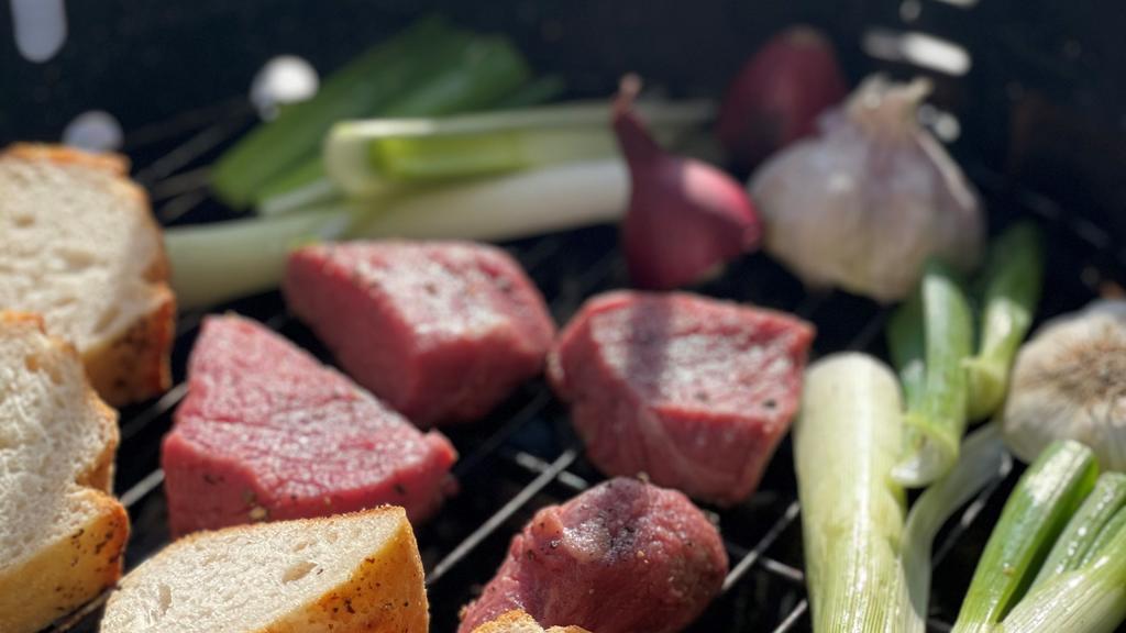 Grill mit Baguette, Steak, Lauch, Zwiebeln und Knoblauch