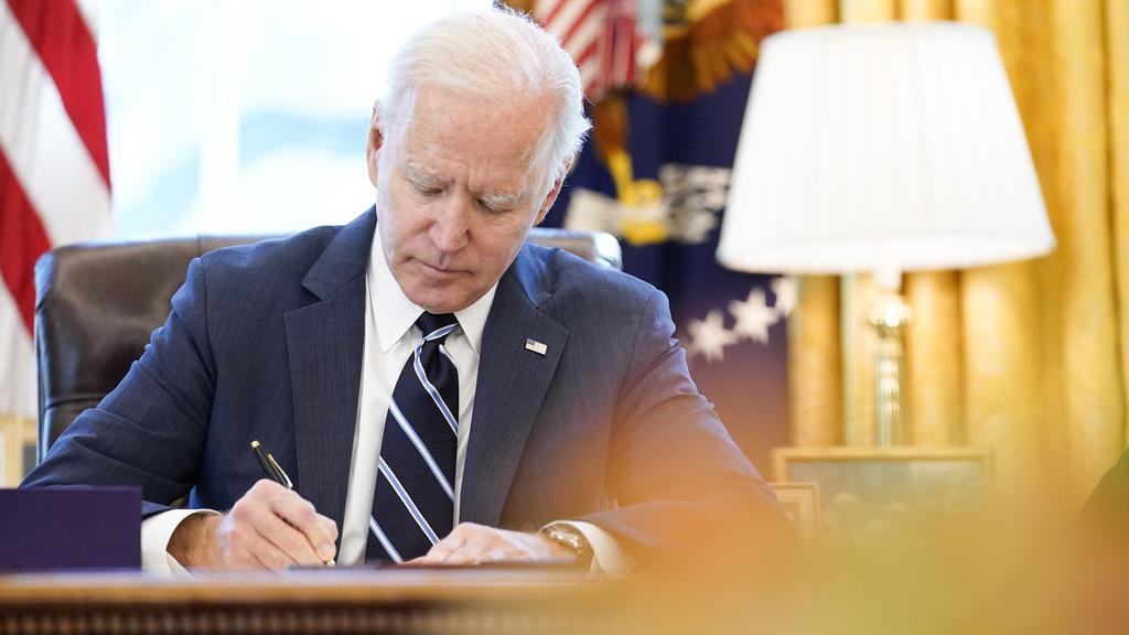ARCHIV - 11.03.2021, USA, Washington: Joe Biden, Präsident der USA, setzt im Oval Office ein billionenschweres Corona-Konjunkturpaket mit seiner Unterschrift in Kraft. Foto: Andrew Harnik/AP/dpa +++ dpa-Bildfunk +++
