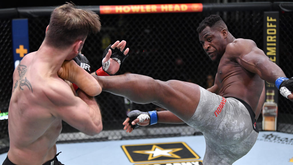 Mar 27, 2021; Las Vegas, NV, USA; Francis Ngannou of Cameroon kicks Stipe Miocic in their UFC heavyweight championship fight during the UFC 260 event at UFC APEX on March 27, 2021 in Las Vegas, Nevada.   Mandatory Credit: Jeff Bottari/Handout Photo v