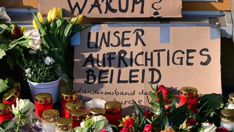 """Blumen, Kerzen und ein Plakat """"Unser Aufrichtiges Beileid"""" liegen vor dem Eingang zur Einrichtung des diakonischen Anbieters Oberlinhaus. Foto: Soeren Stache/dpa-Zentralbild/dpa"""