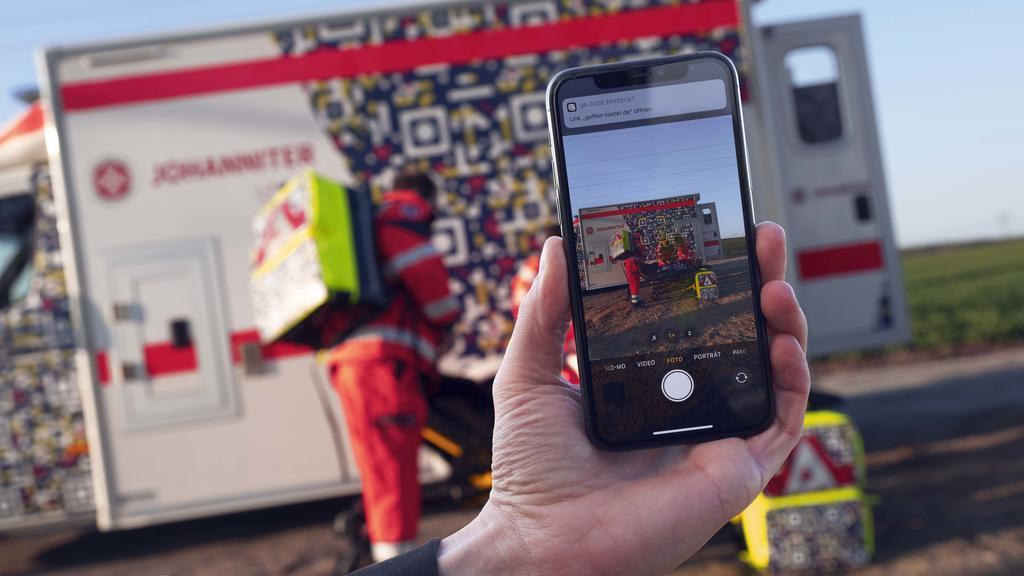 """In einer gestellten Szene der Johanniter-Unfall-Hilfe ist auf einem  Smartphone der QR-Code auf einem Rettungswagen zu sehen, der die Botschaft  """"Gaffen tötet"""" enthält."""