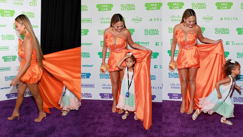 Chrissy Teigens Tochter Luna versteckt sich auf dem roten Teppich unter Mamas Kleid.