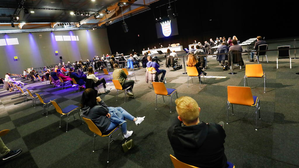 People sit inside the hall on the fairground of Messe Kassel, converted into a court room, on the opening day of the trial against Maurice P., who crashed his car into a carnival parade injuring several people in Volkmarsen on February 25, 2020, in K