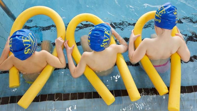 Kinder sitzen beim Schwimmunterricht im Wasser. Foto: Georg Wendt/dpa/Archivbild