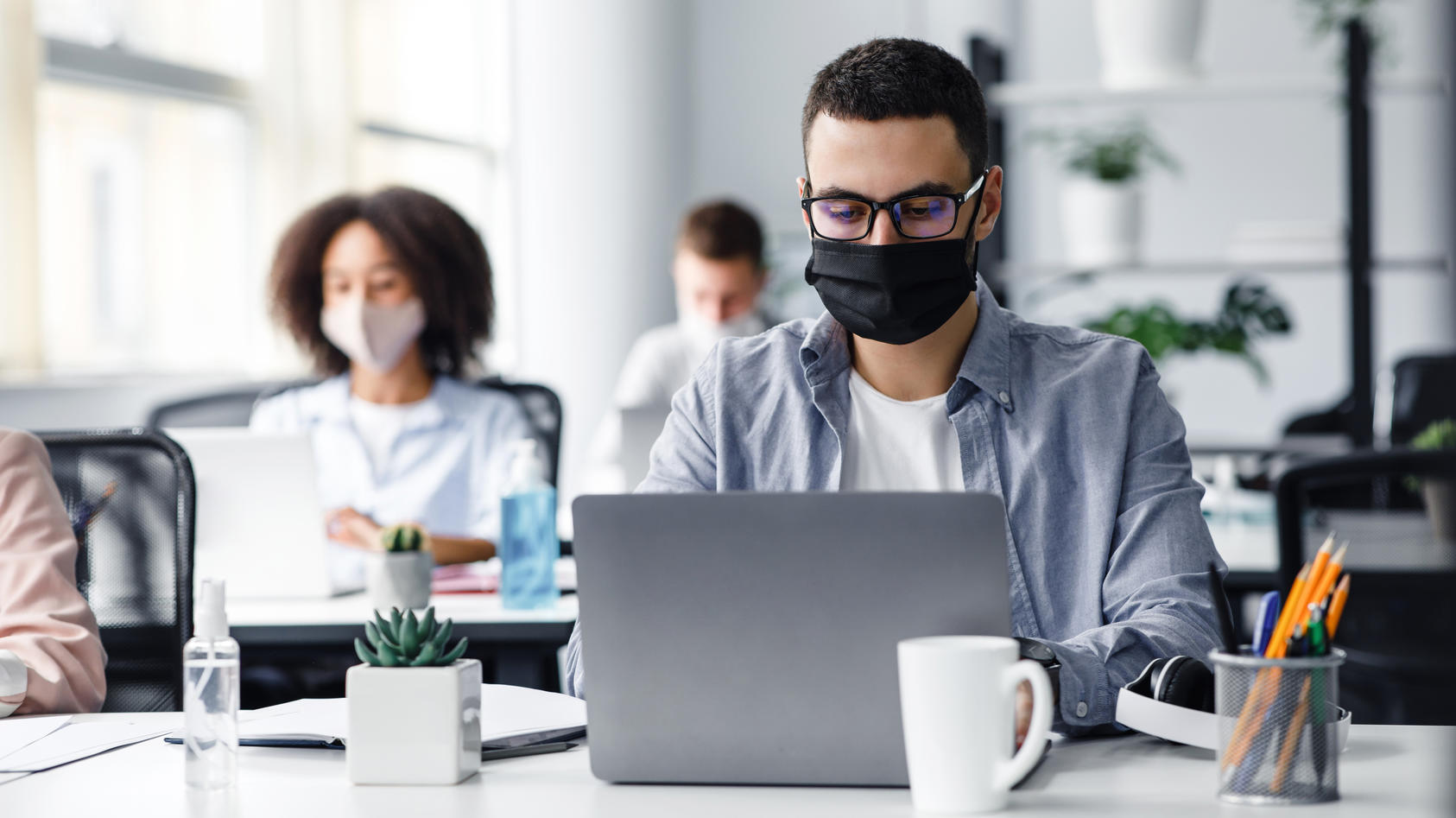 Mit Maske im Büro? Es gibt noch andere Wege, das Infektionsrisiko zu senken. Je nachdem, wo die Angestellten sitzen, ist das unterschiedlich hoch.