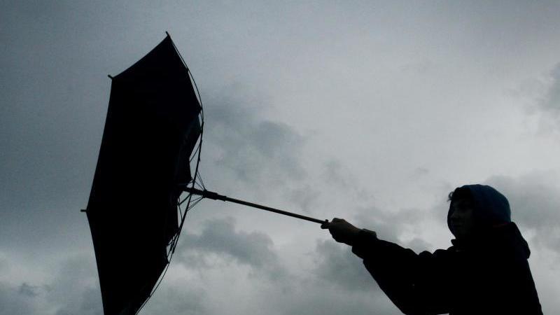 Der Regenschirm eines Spaziergängers wird von einer Windböe erfasst. Foto: picture alliance / Karl-Josef Hildenbrand/dpa/Symbolbild