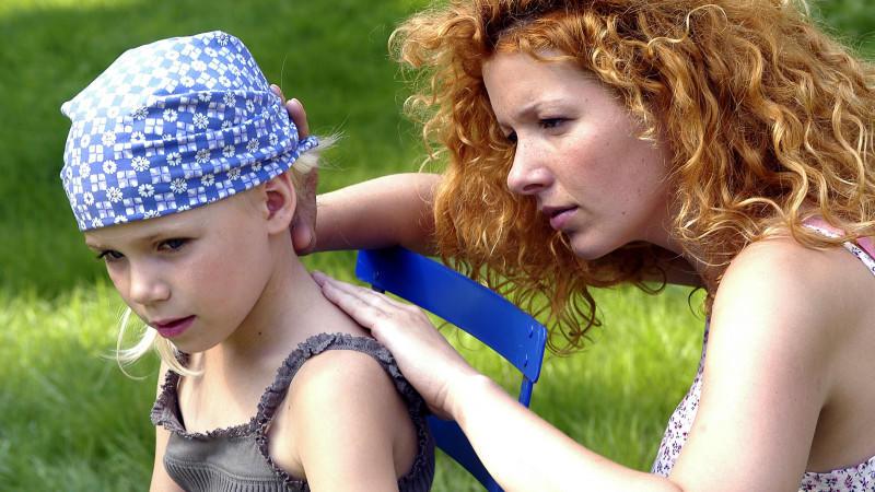 Eine Mutter sucht auf der Haut ihrer kleinen Tochter nach Zecken, aufgenommen 2005. Foto: Chiron Vaccines +++(c) dpa - Report+++