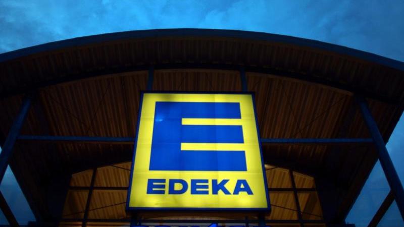 Eine Leuchtreklame weist auf einen Edeka-Markt hin. Foto: Federico Gambarini/dpa/Archivbild
