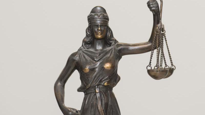 """Eine Figur """"Justitia"""" steht auf einem Tisch. Foto: picture alliance / dpa/Archivbild"""