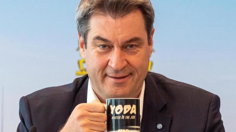 Markus Söder (CSU), Ministerpräsident von Bayern, nimmt vor Beginn der Sitzung des bayerischen Kabinetts, die als Videokonferenz geführt wird, seinen Platz vor einer Fototapete ein. Foto: Peter Kneffel/dpa