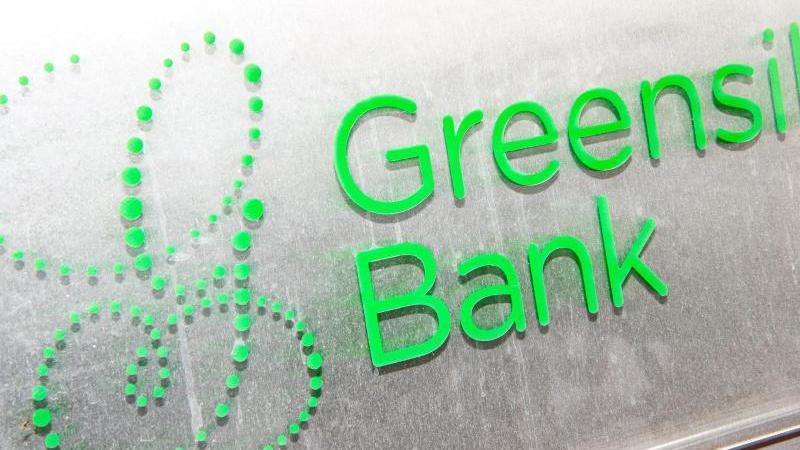 """Ein Schild mit dem Firmennamen """"Greensill Bank"""" hängt am Eingang der Bremer Privatbank. Foto: Sina Schuldt/dpa/Archivbild"""