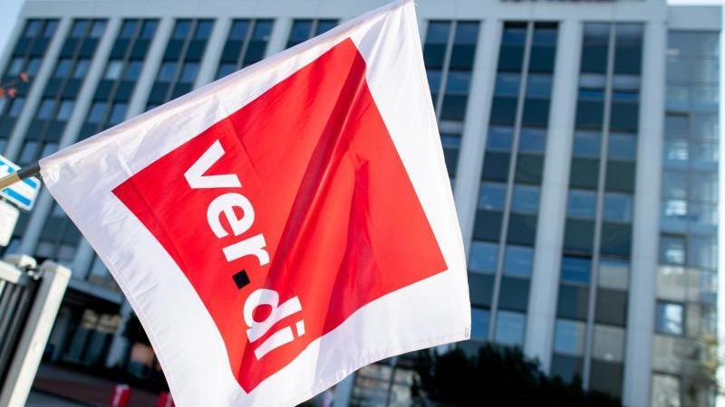 Ein Mitglied der Gewerkschaft Verdi hält an einem Tüv-Standort eine Fahne in den Händen. Foto: Hauke-Christian Dittrich/dpa