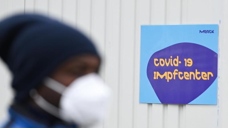 Ein Mitarbeiter des Chemie- und Pharmaunternehmens Merck KGaA steht auf dem Werksgelände vor dem Check-in des Covid-19 Impfcenters. Foto: Arne Dedert/dpa/POOL/dpa