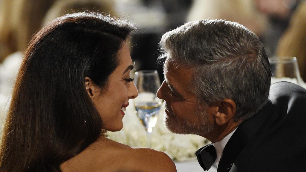 ARCHIV - 07.06.2018, USA, Los Angeles: George Clooney, Schauspieler aus den USA, und seine Frau Amal, Menschenrechtsanwältin aus dem Libanon, sprechen miteinander bei der Verleihung des AFI-Preises für Clooneys Lebenswerk. Er führt Regie, steht vor d