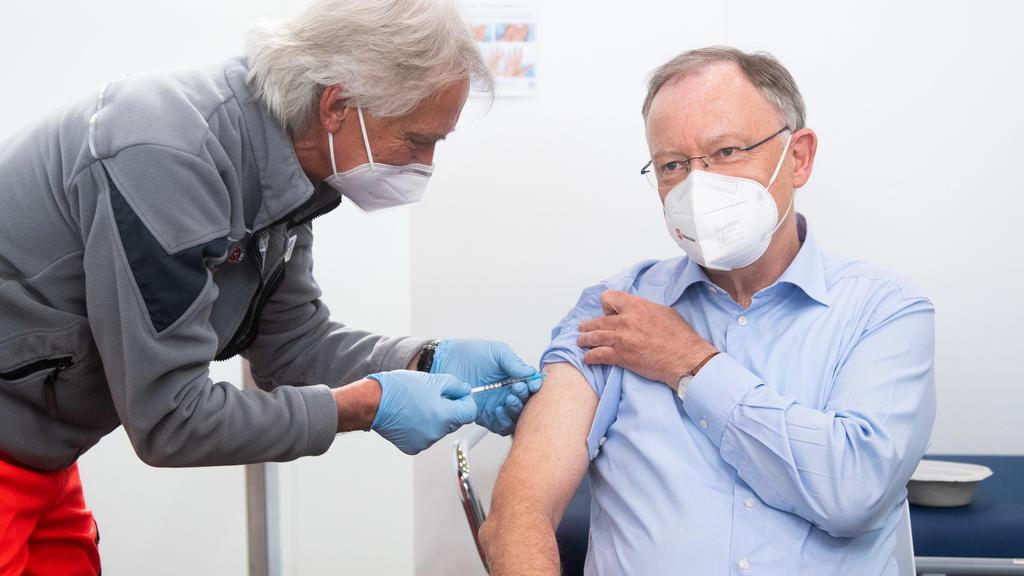 Niedersachsen, Hannover: Stephan Weil (r, SPD), Ministerpräsident Niedersachsen, wird von Rettungsassistent Joachim Gerhardy bei seinem seinem Impftermin im Impfzentrum auf dem Messgelände Hannover mit dem Impfstoff AstraZeneca gegen das