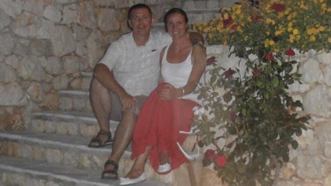 Caroline und ihr Mann Roy sitzen zusammen auf einer Treppe.