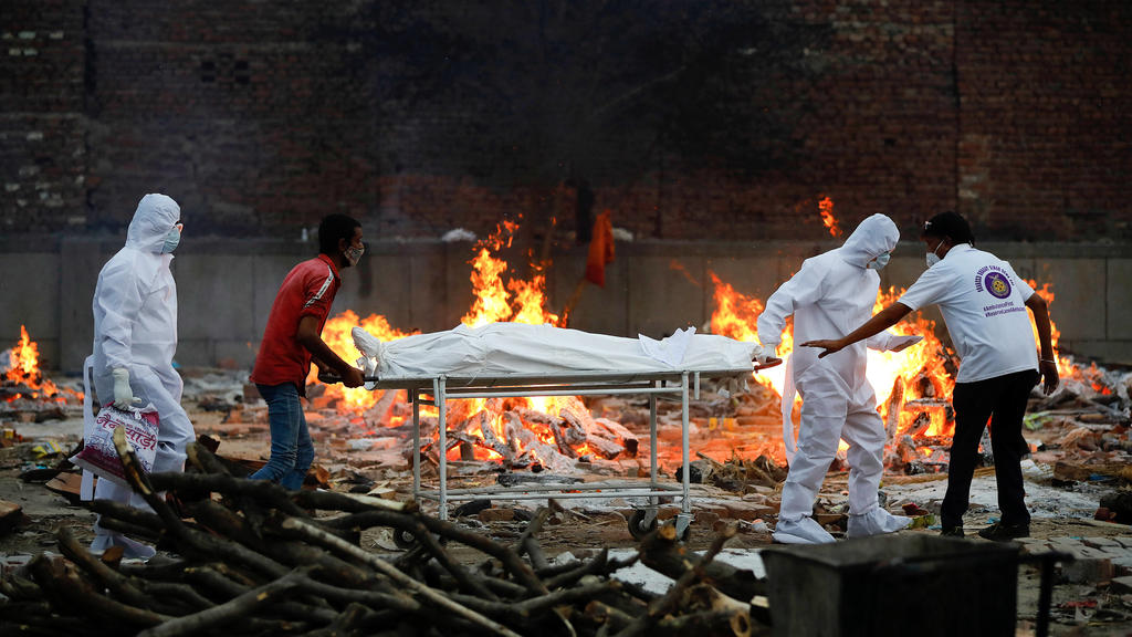 May 9, 2021, Delhi, India: Relatives and health workers carry a body of coronavirus Covid-19 victim during a cremation at a crematorium in New Delhi..India reports 3,66,161 new cases, 3,754 deaths in the last 24 hours. Delhi India - ZUMAs197 20210509