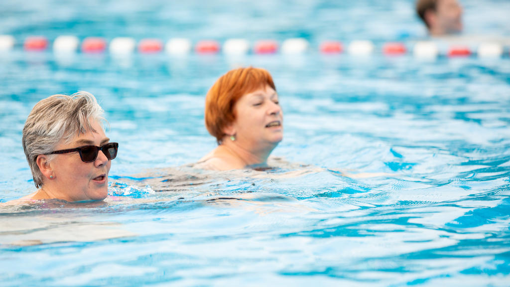 Zwei Frauen schwimmen in einem Becken.