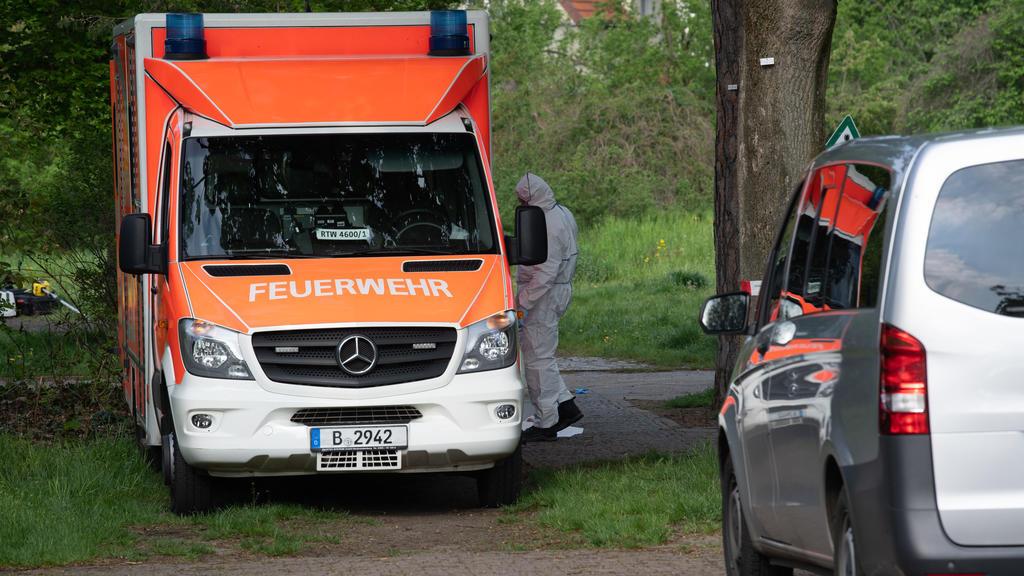 15.05.2021, Berlin: Ein Kriminaltechniker der Polizei steht an einem Rettungswagen unweit einer Parkanlage an der Idsteiner Straße Ecke Seibtweg in Berlin-Zehlendorf . Dort wurde am frühen Morgen ein schwer verletzter Mann gefunden.  Bei einem Streit
