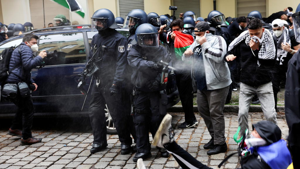 A police officer uses a pepper spray against a man during a demonstration to mark the Nakba and in support of Palestinians, in Berlin, Germany May 15, 2021. REUTERS/Christian Mang