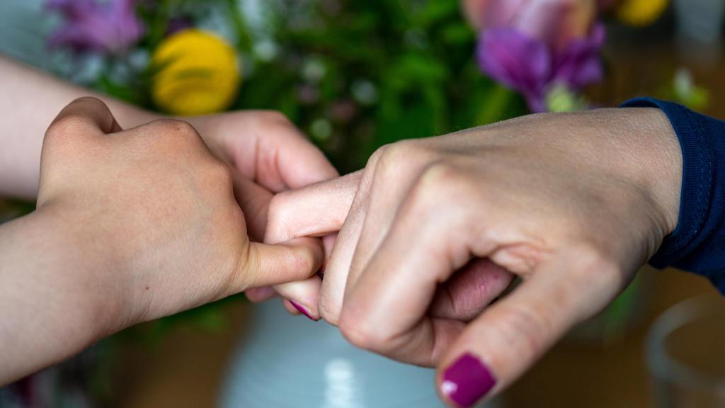 ARCHIV - 07.05.2021, Sachsen, Leipzig: Eine Mutter hält die Hand ihrer Tochter.  Familien sollen die Möglichkeit erhalten, die Namen aller sorgeberechtigten Elternteile in den Pass des Kindes eintragen zu lassen. Das sieht eine Vorlage aus dem Bundes