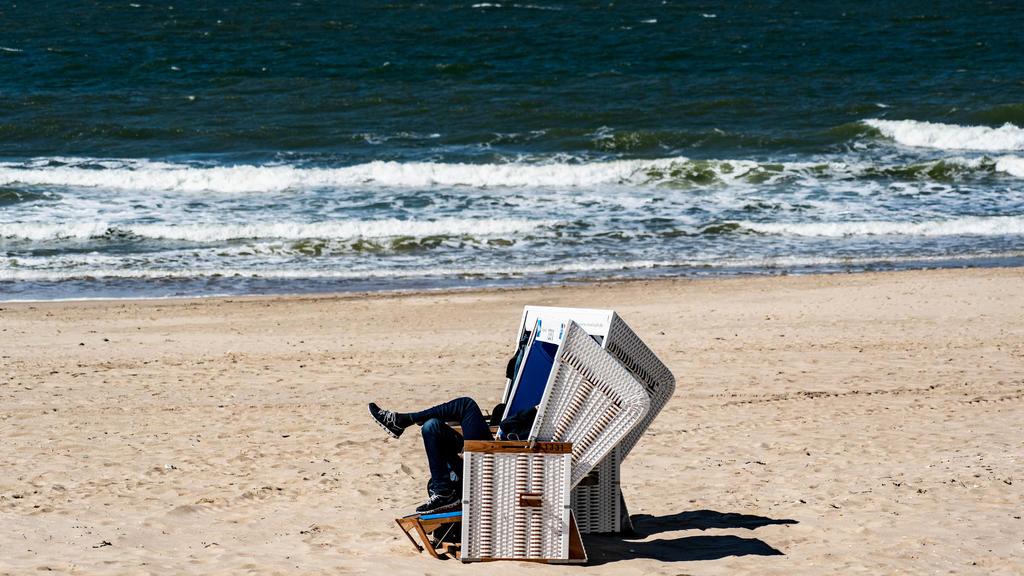 Una silla de playa en la playa de Sylt.  El sol brilla, pero también hay una brisa fresca.