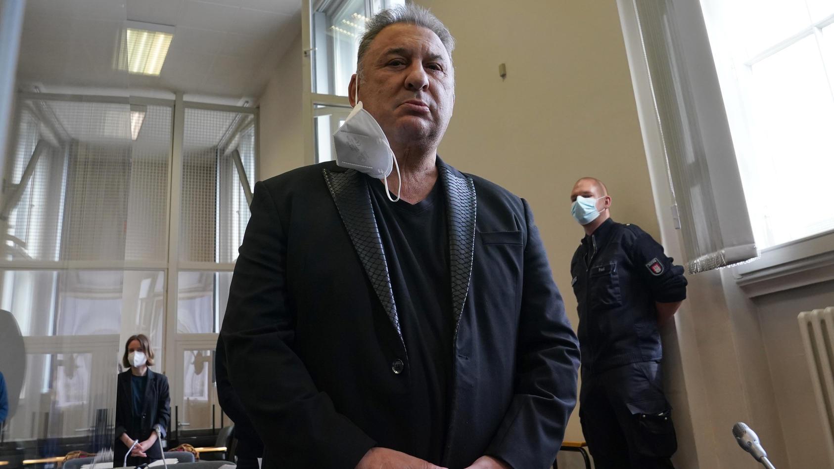 """Der Prozess begann damit, dass """"Milliarden Mike"""" für die Kameras extra seine Maske abgenommen hat, wofür er dann von der Richterin gerügt wurde."""