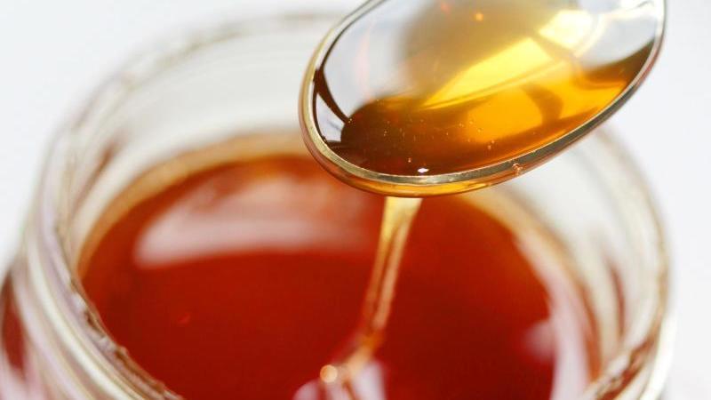 Honig fließt von einen Löffel zurück ins Honigglas.