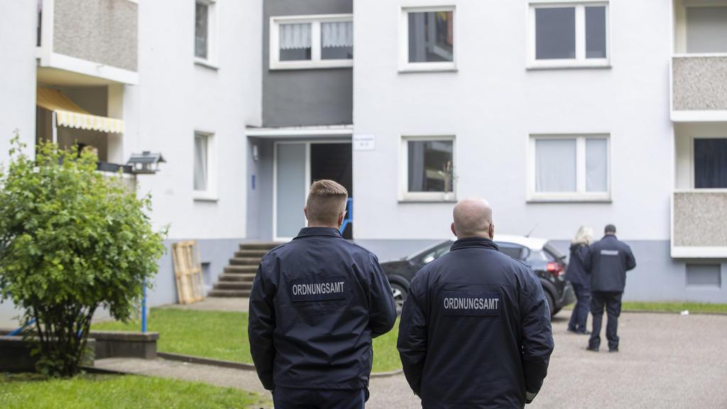 18.05.2021, Nordrhein-Westfalen, Velbert: Mitarbeiter des Ordnungsamt stehen vor einem Eingang eines Hochhauses. Bereits seit Sonntag sind fast 200 Personen aus zwei Hochhäusern unter Quarantäne gestellt. Im Fall der rund 200 Menschen unter Quarantän