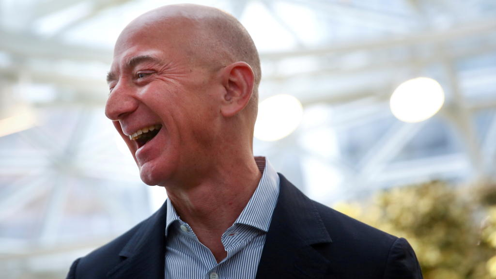 FILE PHOTO: Amazon founder and CEO Jeff Bezos laughs as he talks to the media while touring the new Amazon Spheres during the grand opening at Amazon's Seattle headquarters in Seattle, Washington, U.S., January 29, 2018.   REUTERS/Lindsey Wasson/File
