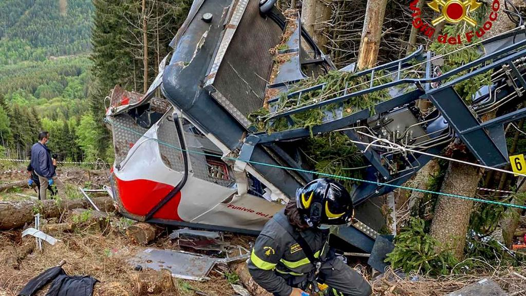 HANDOUT - 23.05.2021, Italien, Stresa: Rettungskräfte arbeiten am Wrack einer abgestürzten Gondel, die in einem Waldstück liegt. Beim Absturz der Gondel einer Seilbahn am norditalienischen Lago Maggiore haben mindestens 14 Menschen ihr Leben verloren