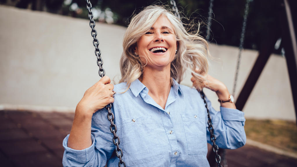Eine ältere Frau mit grauen Haaren sitzt auf einer Schaukel und sieht sehr glücklich aus.