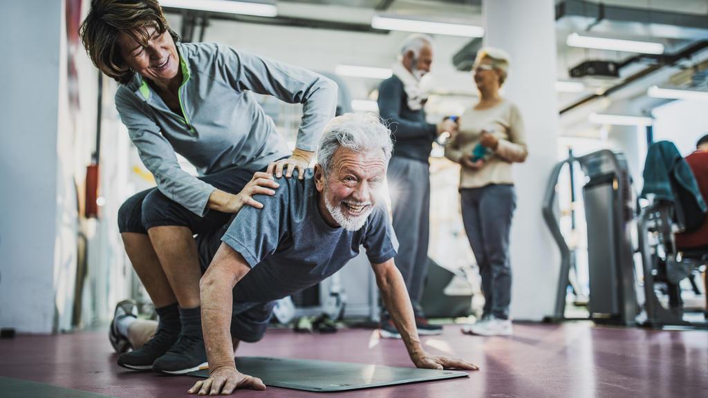 Ein glücklich wirkendes Paar hat Spaß beim Workout im Fitnessstudio, während der Mann eine Liegestütze durchführt.