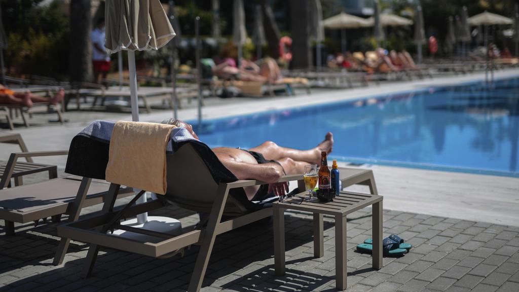"""ARCHIV - 15.06.2020, Spanien, Palma de Mallorca: Ein deutscher Tourist sonnt sich am Schwimmbad des Hotels Riu Concordia in Palma de Mallorca.    (zu dpa """"Tui will Schulden durch Verkauf von Hotel-Beteiligung verringern"""") Foto: Joan Mateu/AP/dpa +++"""