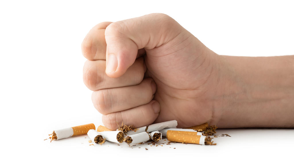 Ein Mann zerstört mit seiner Faust Zigaretten, die auf einem Tisch liegen.
