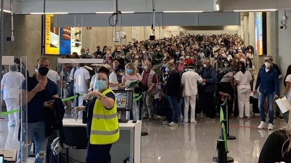 Hunderte Touristen warten dicht gedrängt am Flughafen von Palma de Mallorca.