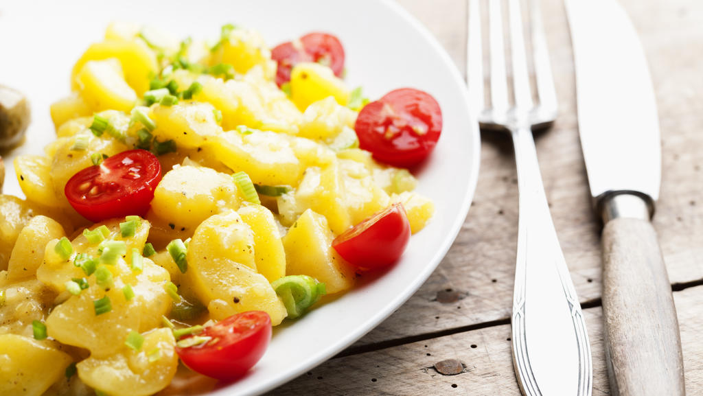 Eine Portion Kartoffelsalat liegt auf einem Teller, daneben sieht man Besteck liegen.