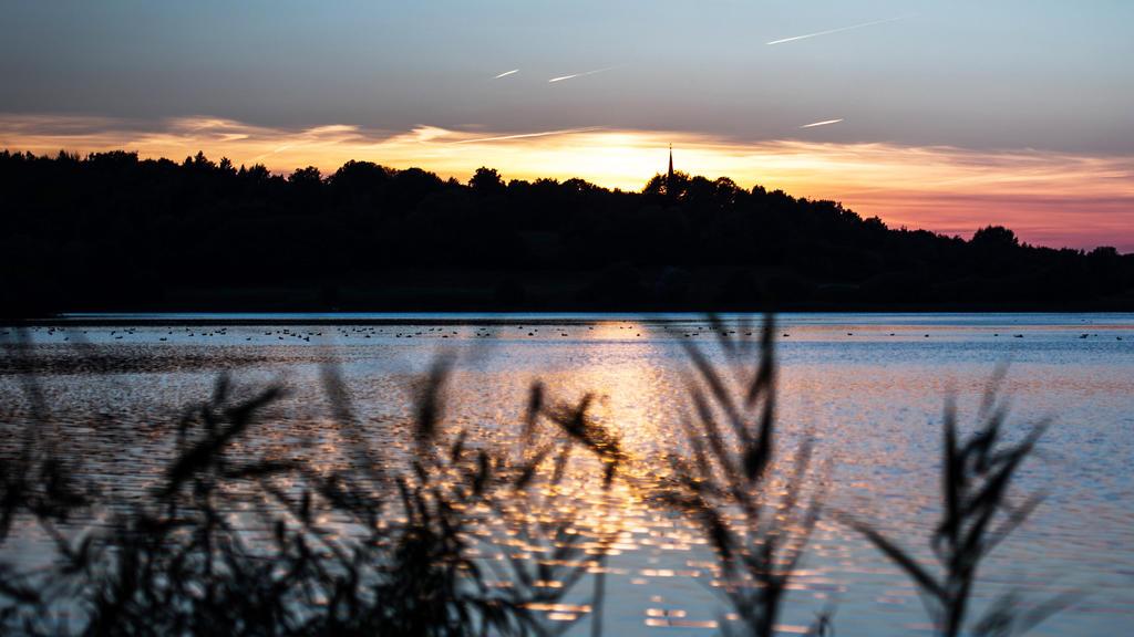 ARCHIV - Die Sonne geht  am 02.10.2013 am kleinen Plöner See in Plön (Schleswig-Holstein) unter. Das Umweltministerium, die Wasser- und Bodenverbände sowie die Gemeinden in Schleswig-Holstein unterzeichneten eine Zielvereinbarungen für den besseren S