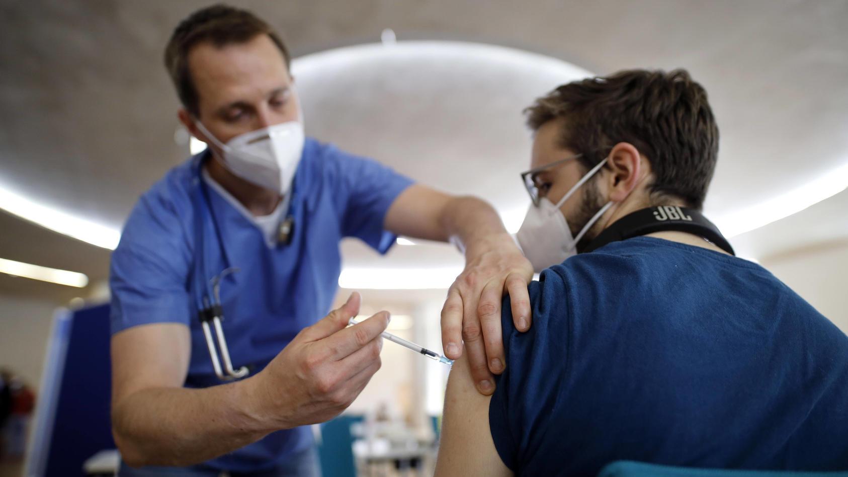 Ein Mann bekommt seine Impfung in Köln.