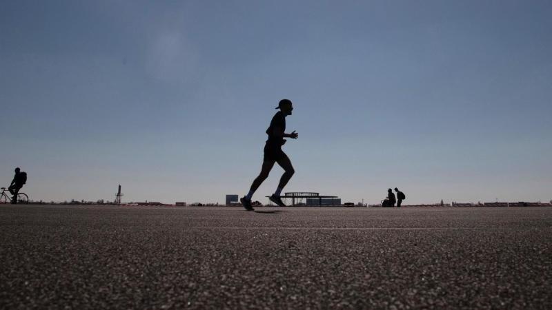 Ein Mann läuft bei Sonnenschein über das Tempelhofer Feld. Foto: Paul Zinken/dpa-Zentralbild/dpa/Archivbild