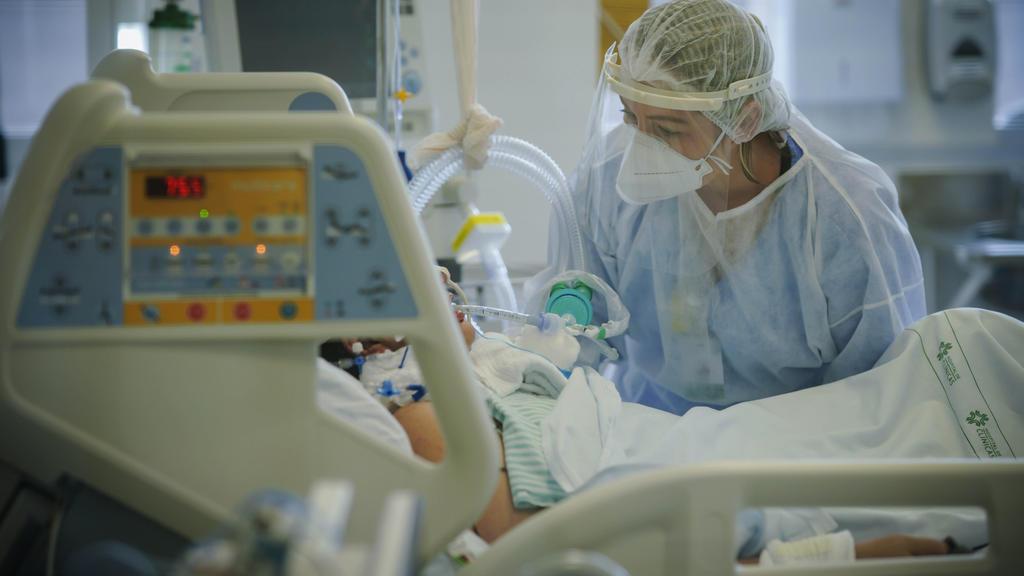 ARCHIV - 19.03.2021, Brasilien, Porto Alegre: Ein medizinische Mitarbeiterin behandelt im Krankenhaus «Hospital das Clinicas» einen Covid-19-Patienten auf der Intensivstation. (zu dpa «Studie: Einsatz von Antibiotika bei Covid-19-Patienten oft unnöti