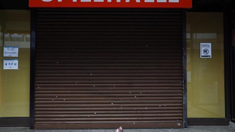 Eine einzelne Taube sitzt vor einer geschlossenen Spielhalle. Foto: Nicolas Armer/dpa/Archivbild