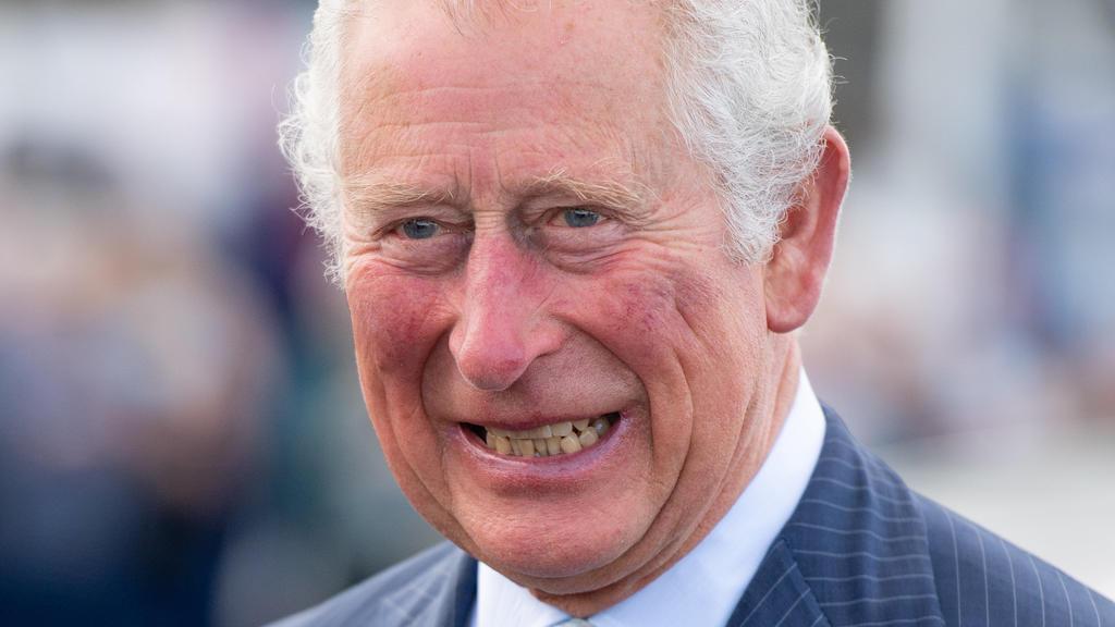 19.05.2021, Großbritannien, Donaghadee: Der britische Prinz Charles, Prinz von Wales, lacht bei einem Besuch im Hafen von Donaghadee, wo er Steine besichtigte, die die Hafenmauern säumen und während der Pandemie von den Menschen vor Ort mit Botschaft