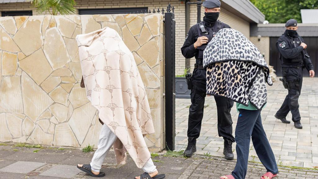 08.06.2021, Nordrhein-Westfalen, Leverkusen: Polizisten stehen vor einer Villa, während zwei Personen mit Decken über dem Oberkörper das Gelände verlassen. Bei Ermittlungen gegen Clankriminalität durchsuchten Spezialkräfte der Polizei rund 30 Objekte